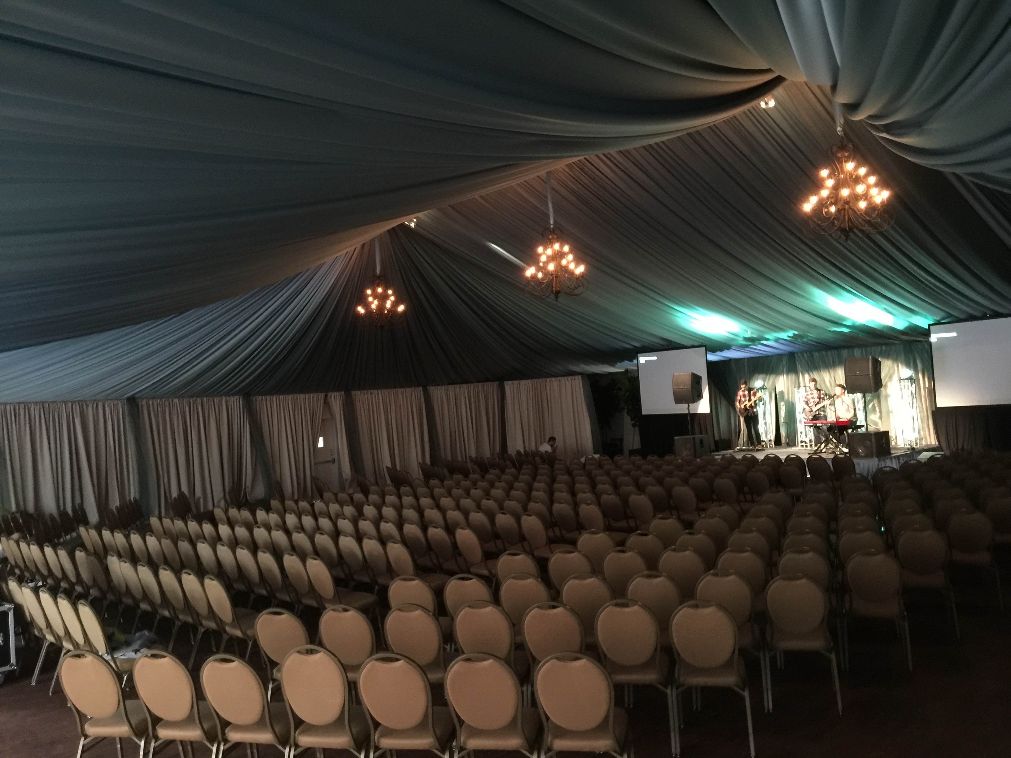 Elegant conference center tent equipped with chandelier, conference seating, and curtain detail.
