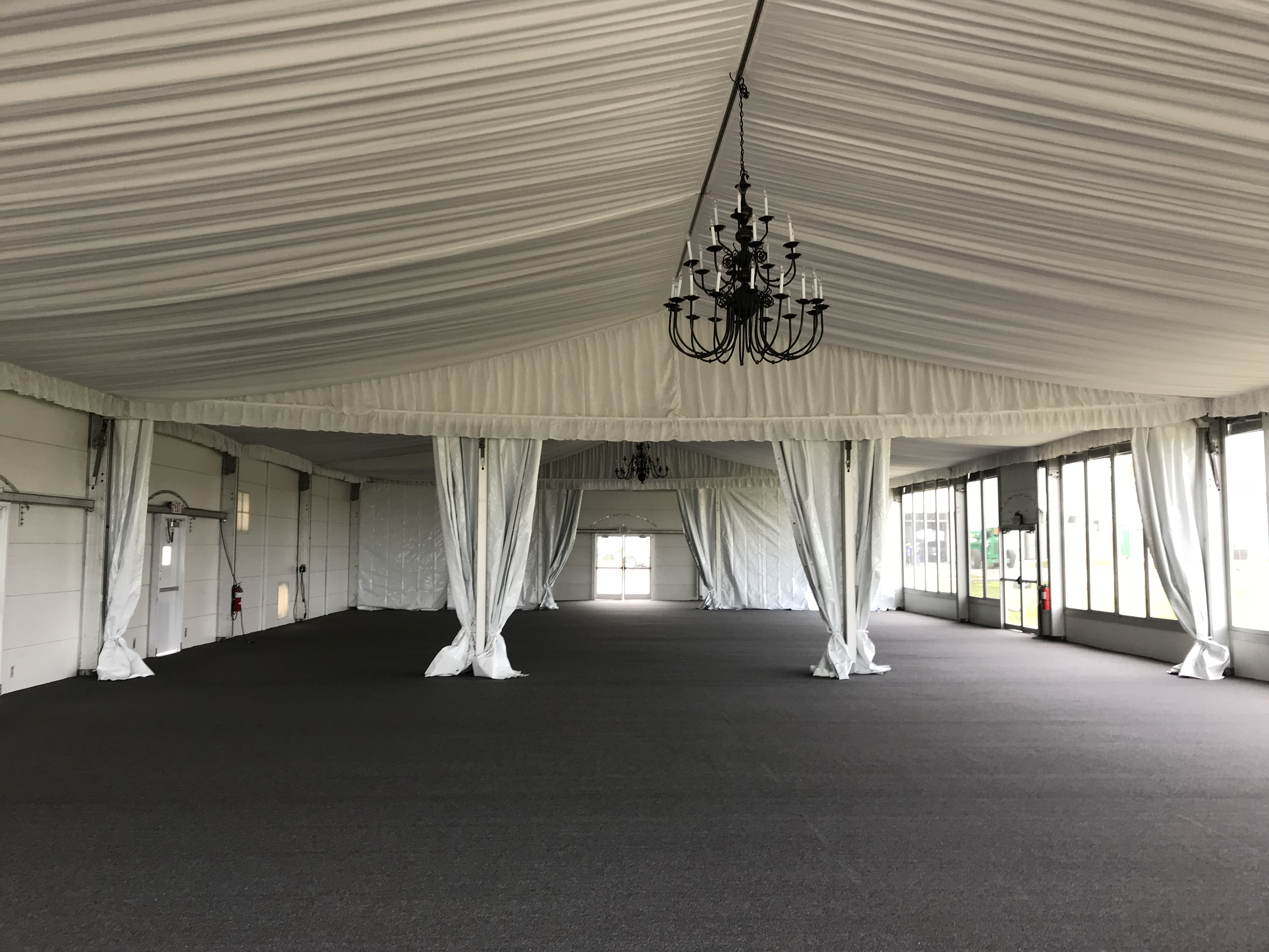 Indoor View of Outdoor Temporary Structure used for Hurricane Harvey Relief Efforts Ceiling is draped in Curtains with Chandelier